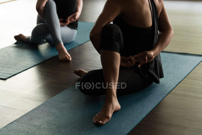Women practicing yoga on exercise mats in fitness studio. — Stock Photo