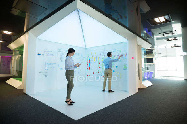 Male and female executives working together in futuristic office — Stock Photo