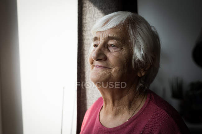 Thoughtful senior woman standing near window at home — Stock Photo
