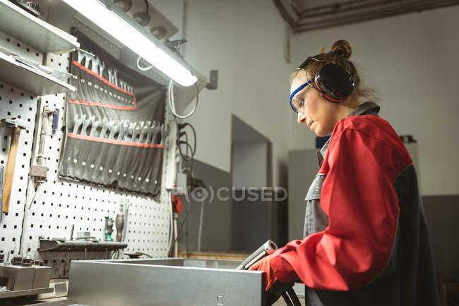 Arbeiterin repariert Maschine mit Werkzeug in Fabrik — Stockfoto