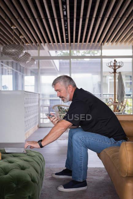 Чоловічий office виконавчий говорити на мобільному телефоні під час користування цифровий планшет на дивані в творчих pffice — стокове фото