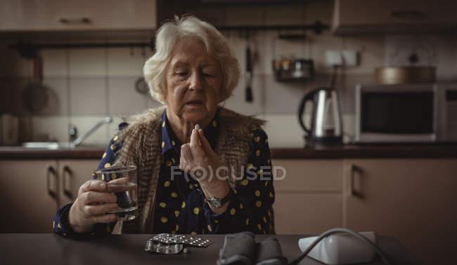 Femme âgée ayant pilule dans la cuisine à la maison — Photo de stock