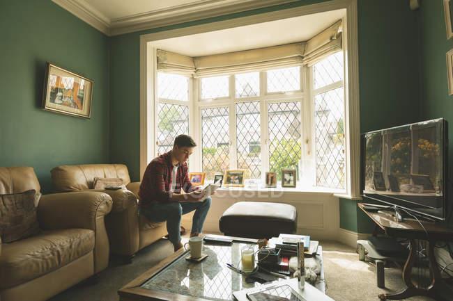 Человек читает книгу на диване в гостиной дома . — стоковое фото