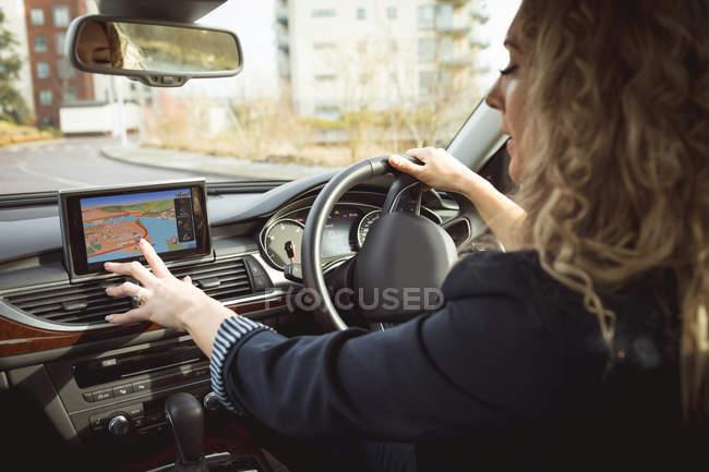 Hermosa mujer ejecutiva utilizando la navegación mientras conduce un coche - foto de stock