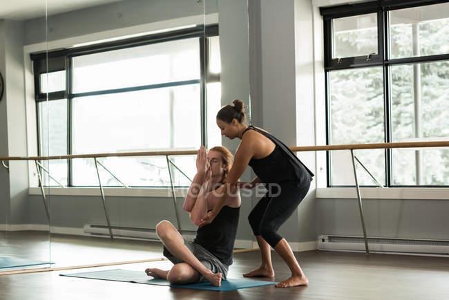 Тренер помогает человеку практиковать акройогу в фитнес-студии . — стоковое фото
