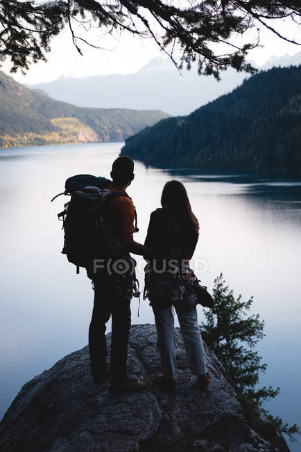 Rear view of couple with bag pack standing on rock — Stock Photo