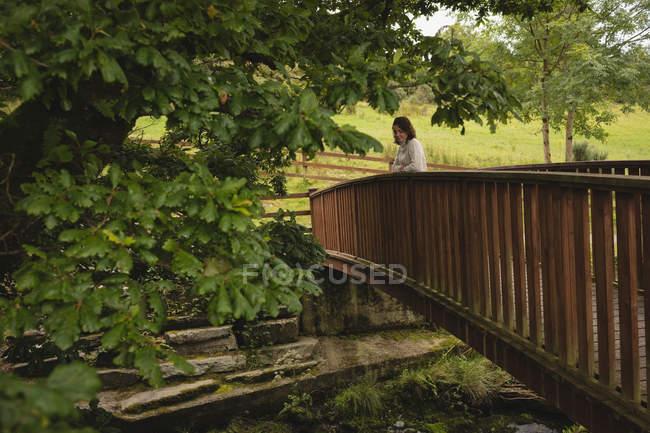 Bella donna in piedi sul ponte pedonale — Foto stock
