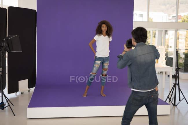 Fotógrafo profesional tomando foto de modelo en estudio - foto de stock