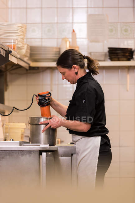 Chef blending with hand blender in the commercial kitchen — Stock Photo