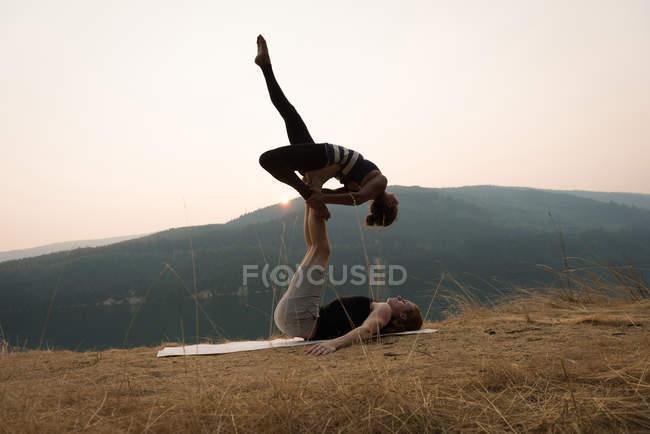 Спортивная пара, практикующая акро-йогу на пышной зеленой земле во времена Двана — стоковое фото