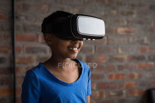 Happy pre-adolescent girl using virtual reality headset in office. — Stock Photo