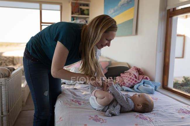 Happy mother playing with baby boy at home. — Stock Photo