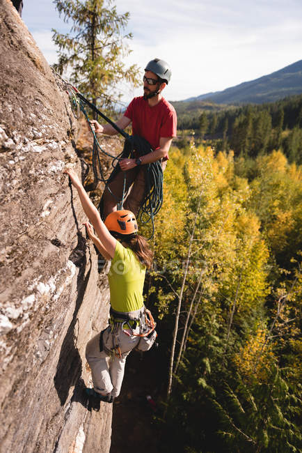 Determined couple climbing up the rocky mountain — Stock Photo