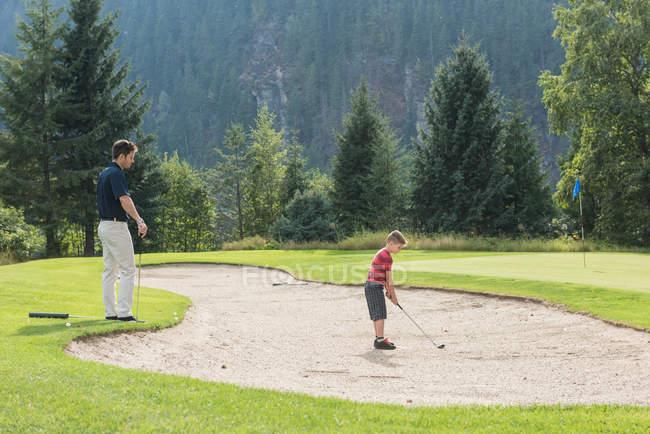 Père aidant son fils à jouer au golf dans le parcours — Photo de stock