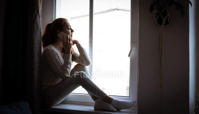 Teenager-Mädchen sitzt auf Fensterbank und telefoniert zu Hause — Stockfoto