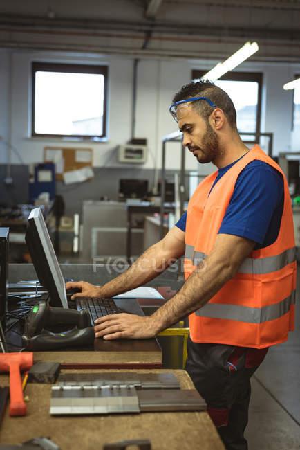 Männliche Arbeiter arbeiten in der Fabrik am Computer — Stockfoto