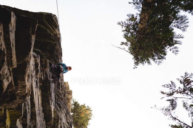 Путешественник готовится подняться на скалистую гору в лесу — стоковое фото