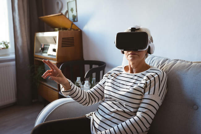 Senior woman wearing a virtual reality headset while relaxing on a sofa — Stock Photo