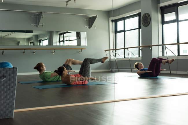 Grupo de atletas em forma praticando ioga no estúdio de fitness . — Fotografia de Stock