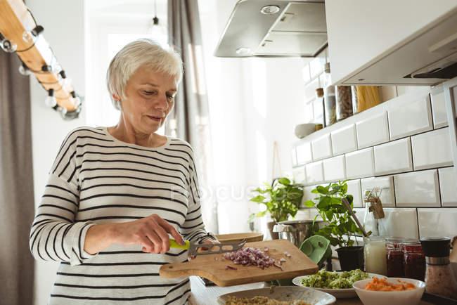Haute femme ajoutant coupe des oignons dans un bol dans la cuisine — Photo de stock