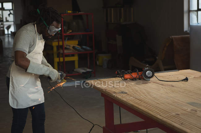 Carpenter cutting metal with electric saw in workshop — Stock Photo