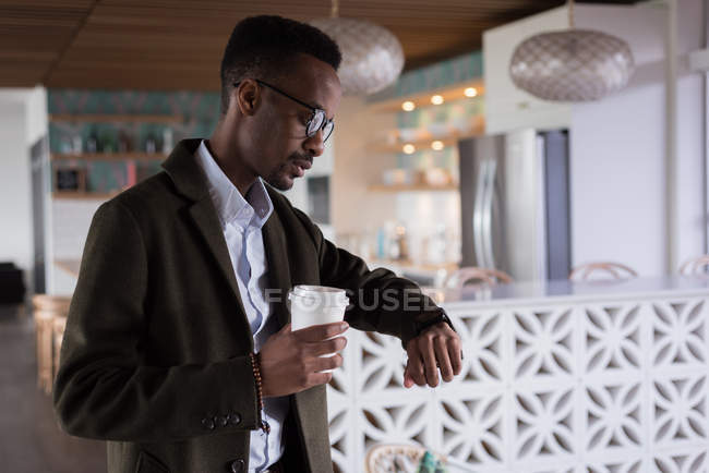 Businessman looking at smartwatch while having coffee in cafeteria at creative office — Stock Photo