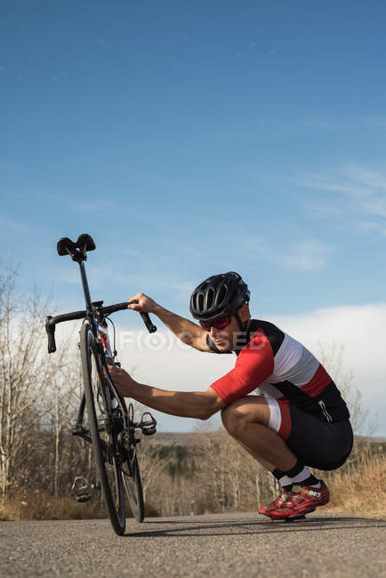 Biker checking his mountain bike on road on a sunny day — Stock Photo