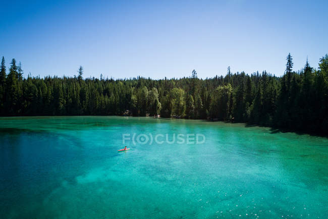 Kayaker kayaking in shallow turquoise water on a sunny day — Stock Photo