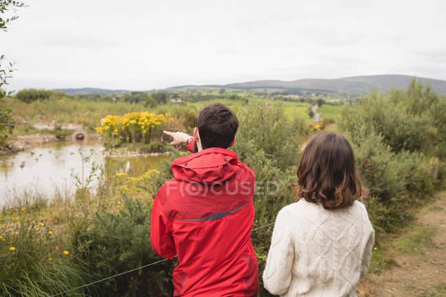 Coppia che interagisce con l'altro vicino stagno in campagna — Foto stock