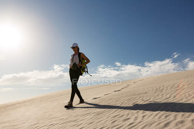 Female hiker with backpack walking on sand on a sunny day — Stock Photo