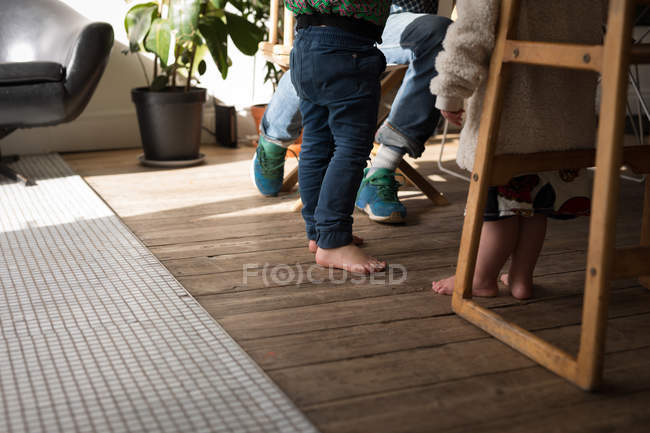Low section of father with kids in living room at home. — Stock Photo