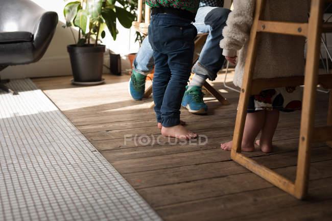 Низкая часть отца с детьми в гостиной дома . — стоковое фото