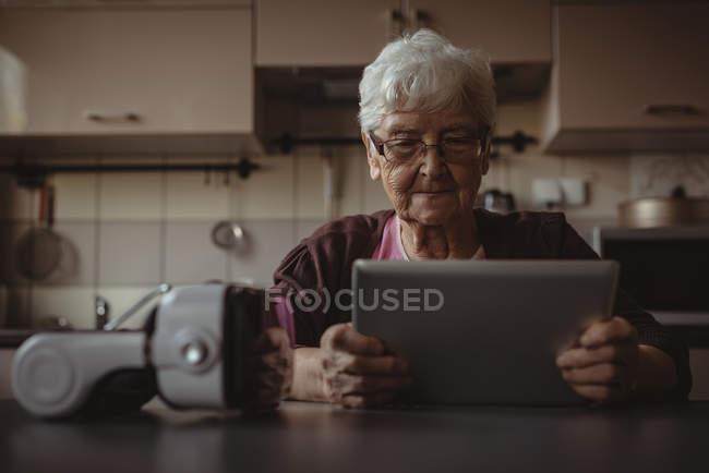Femme âgée utilisant une tablette numérique dans la cuisine à la maison — Photo de stock