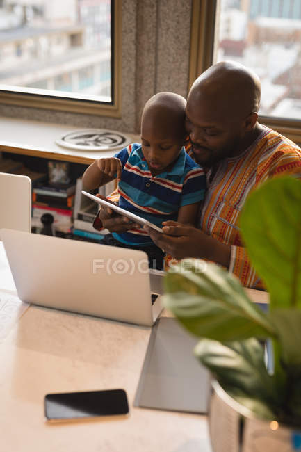 Щасливий батько і син, використовуючи цифровий планшетний столом з ноутбука. — стокове фото