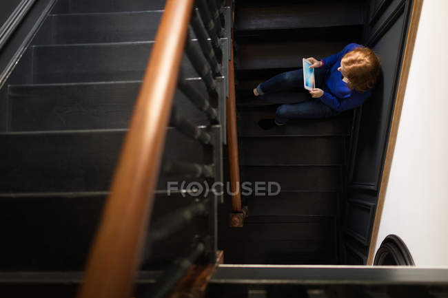 Over head view of woman sitting on the staircase and using tablet — Stock Photo
