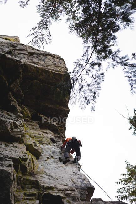 Alpinista determinado escalando a montanha rochosa — Fotografia de Stock