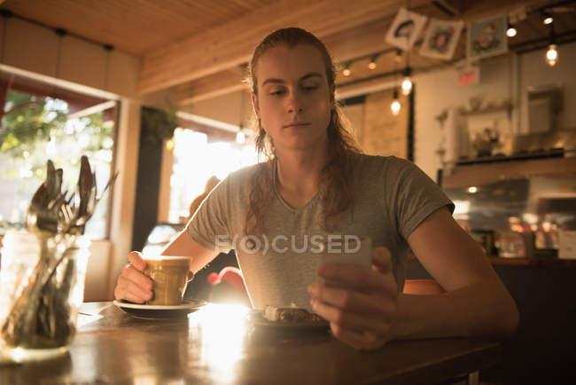 Человек, с помощью мобильного телефона имея кофе в cafetria — стоковое фото