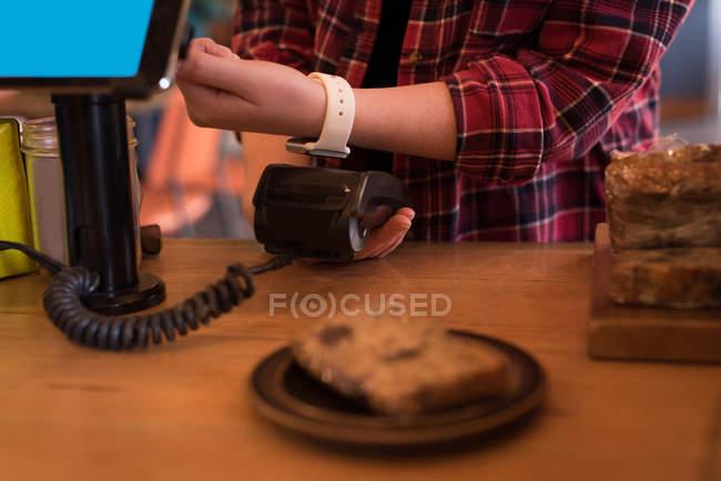 Client d'effectuer le paiement avec smartwatch au comptoir de café — Photo de stock