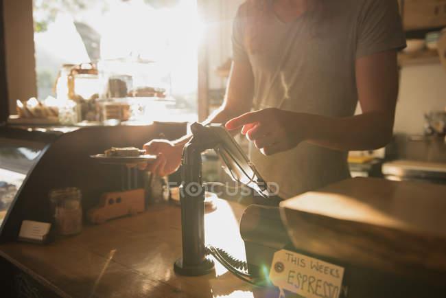 Средняя секция официантов, принимающих заказ на цифровой планшет в кафетерии — стоковое фото