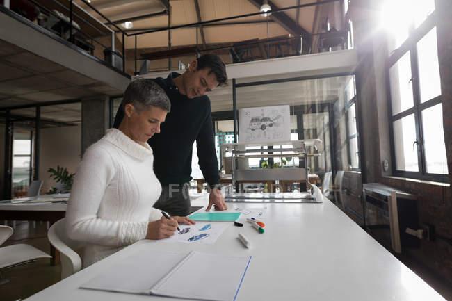 Collègues de travail, discuter au croquis au bureau. — Photo de stock