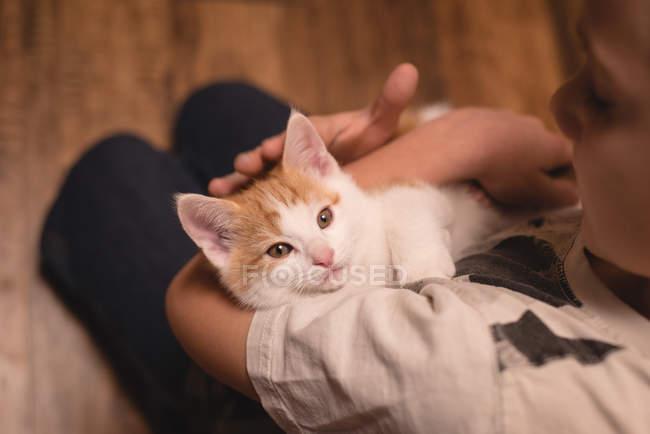Junge hält ihre Katze im Wohnzimmer zu Hause — Stockfoto