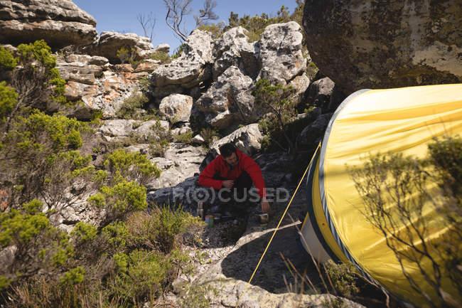 Randonneur assis dehors préparant à boire pendant la pause en montagne — Photo de stock