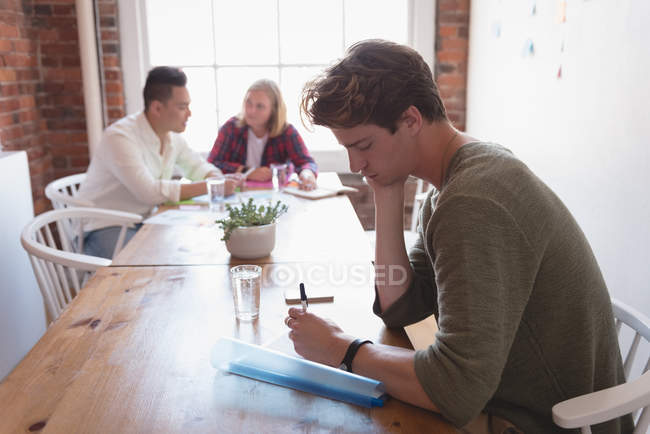 Male executive writing on paper and colleagues discussing in background at office — Stock Photo