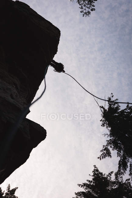 Low angle view of rock climber climbing the rocky cliff against sun — Stock Photo