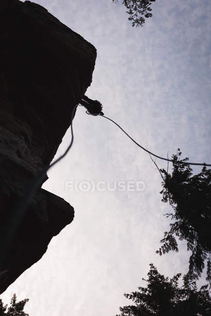 Vista de ángulo bajo del escalador escalando el acantilado rocoso contra el sol - foto de stock
