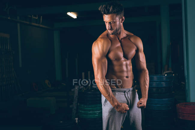 Muscular man flexing his muscles in fitness studio — Stock Photo