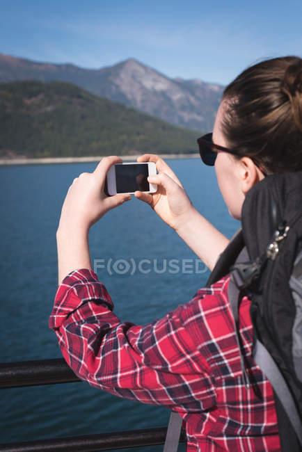 Задній вид малюнок беручи жінка з мобільного телефону на сонячний день — стокове фото