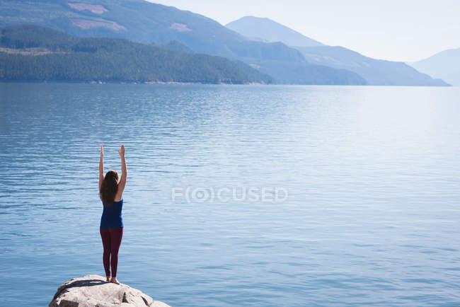 Mujer practicando yoga en roca cerca del mar - foto de stock