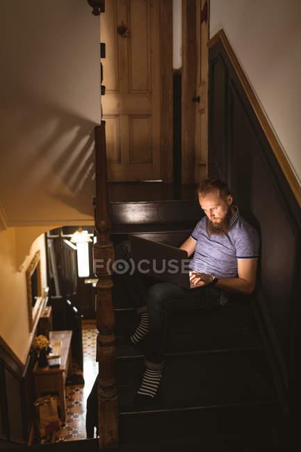 Человек, использующий свой ноутбук, сидя дома на лестнице — стоковое фото