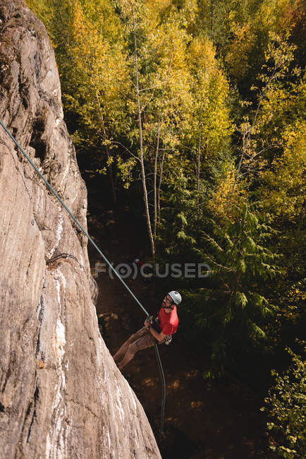 Решительный скалолаз, взбирающийся на скалистую гору — стоковое фото